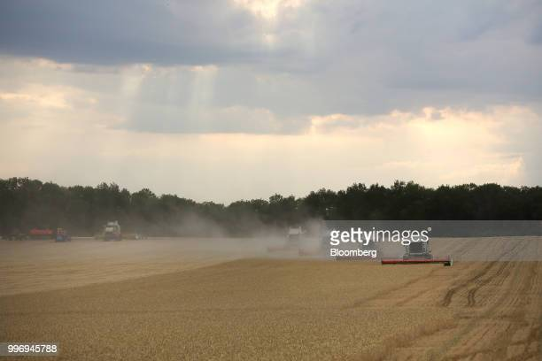 Tucano combine harvesters manufactured by Claas KGaA drive through a field of wheat during the summer harvest on a farm operated by Ros Agro Plc in...
