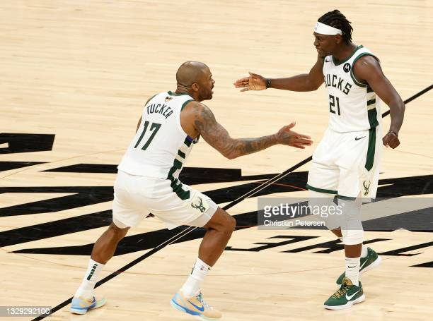 Tucker and Jrue Holiday of the Milwaukee Bucks celebrate a team win against the Phoenix Suns in Game Five of the NBA Finals at Footprint Center on...