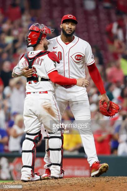 Tucker Barnhart and Amir Garrett of the Cincinnati Reds celebrate after beating the New York Mets 4-3 at Great American Ball Park on July 20, 2021 in...