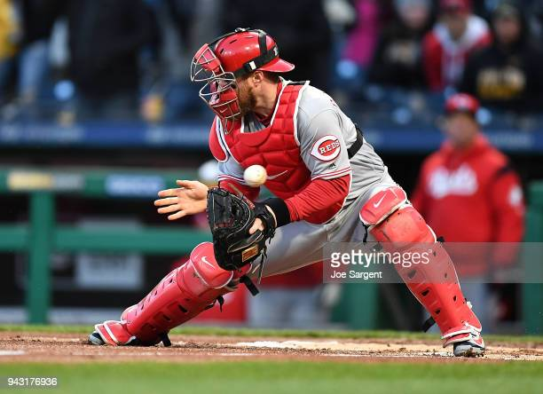 Tucker Barnhart of the Cincinnati Reds can't field a throw by Jesse Winker allowing Josh Bell of the Pittsburgh Pirates to score during the first...