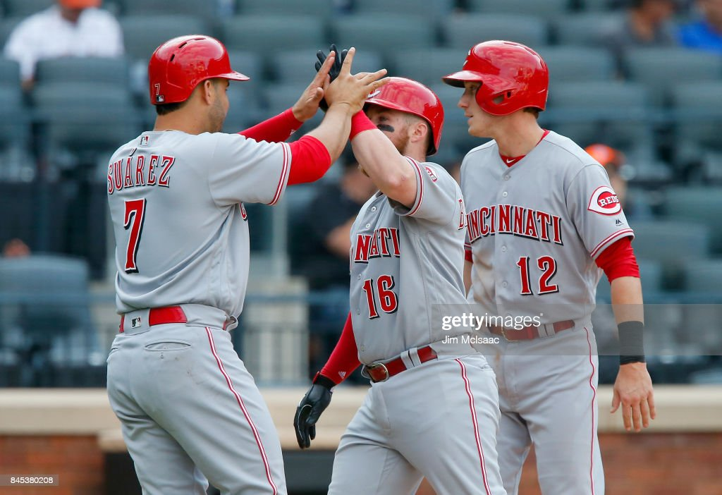 Tucker Barnhart #16 of the Cincinnati Reds celebrates his ninth-inning, three-run home run against the New York Mets with teammates Zach Vincej #12 and Eugenio Suarez #7 at Citi Field on September 10, 2017 in the Flushing neighborhood of the Queens borough of New York City.