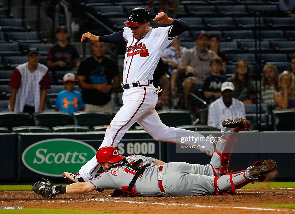 Tucker Barnhart #16 of the Cincinnati Reds dives to tag homeplate for a force out on Freddie Freeman #5 of the Atlanta Braves on a grounder hit by Jace Peterson #8 of the Atlanta Braves in the 11th inning at Turner Field on June 15, 2016 in Atlanta, Georgia.