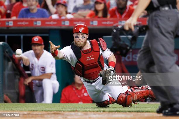 Tucker Barnhart of the Cincinnati Reds flips the ball toward the plate after a wild pitch by Homer Bailey allowed a run to score in the first inning...
