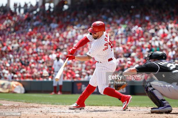 Tucker Barnhart of the Cincinnati Reds hits single to left center field to drive in a run against the Colorado Rockies in the second inning at Great...