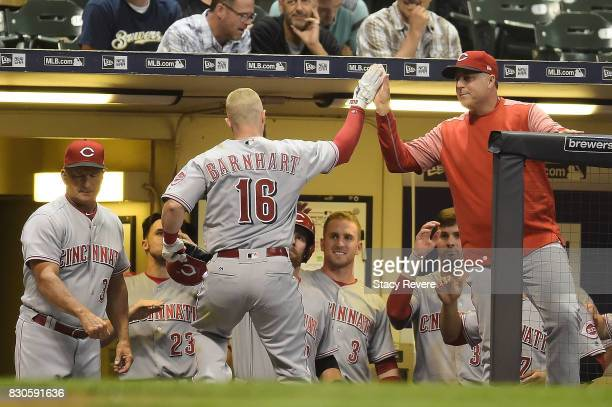 Tucker Barnhart of the Cincinnati Reds is congratulated by manager Bryan Price following a home run during the seventh inning of a game against the...