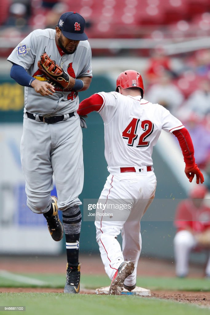 Tucker Barnhart #16 of the Cincinnati Reds makes contact with Jose Martinez #38 of the St. Louis Cardinals on a play at first base in the ninth inning of the game at Great American Ball Park on April 15, 2018 in Cincinnati, Ohio. The Cardinals won 3-2. All players are wearing #42 in honor of Jackie Robinson Day.