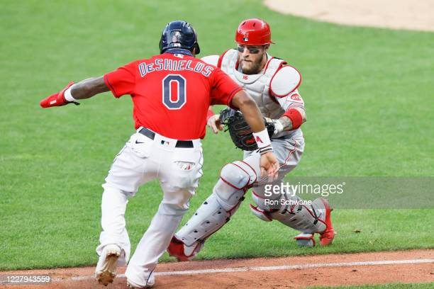 Tucker Barnhart of the Cincinnati Reds tags out Delino DeShields of the Cleveland Indians in a rundown in the seventh inning at Progressive Field on...