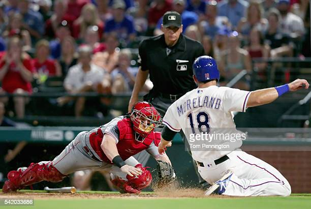 Tucker Barnhart of the Cincinnati Reds tags out Mitch Moreland of the Texas Rangers at home plate in the bottom of the eighth inning at Globe Life...