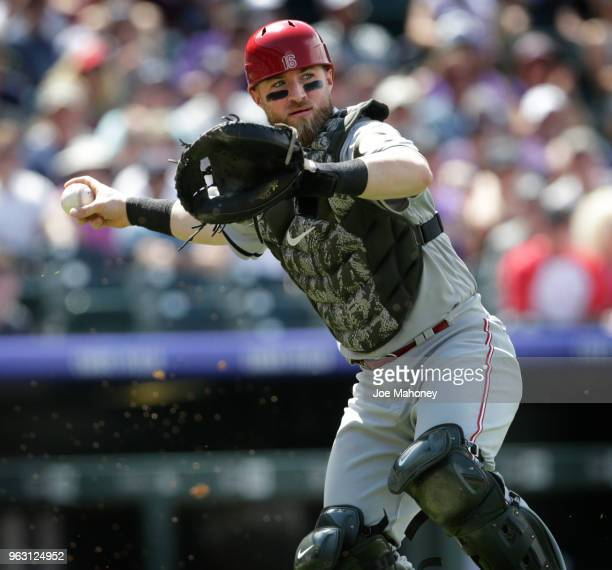 Tucker Barnhart of the Cincinnati Reds throws to first base to put out German Marquez of the Colorado Rockies on an attempted bunt in the sixth...