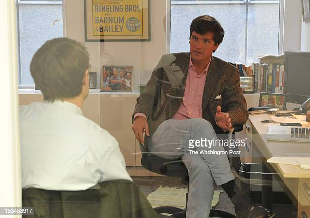 Tucker Carlson, R, talks with Jon Ward at the office of the new conservative website, the Daily Caller, on January 6 in Washington, DC. The site, at...