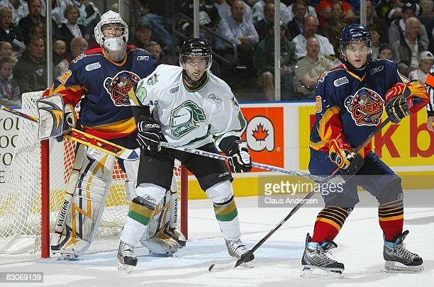 Tucker Hunter of the London Knights sets up between Jaroslav Janus and Tyler Hostetter of the Erie Otters in a game played at the John Labatt Centre...
