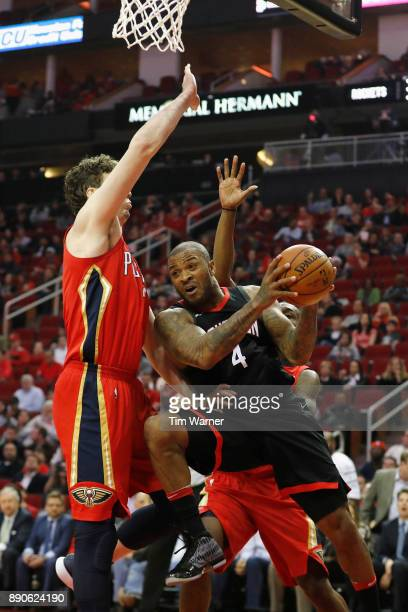 Tucker of the Houston Rockets drives to the basket defended by Omer Asik of the New Orleans Pelicans Jalen Jones in the first half at Toyota Center...
