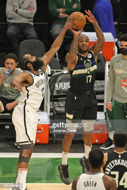 Tucker of the Milwaukee Bucks shoots over James Harden of the Brooklyn Nets at Fiserv Forum on June 17, 2021 in Milwaukee, Wisconsin. The Bucks...
