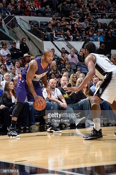 PJ Tucker of the Phoenix Suns controls the ball against Kawhi Leonard of the San Antonio Spurs at the ATT Center on November 6 2013 in San Antonio...