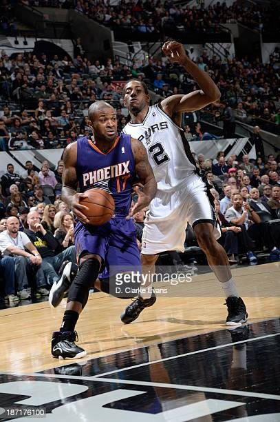 PJ Tucker of the Phoenix Suns drives to the basket against Kawhi Leonard of the San Antonio Spurs at the ATT Center on November 6 2013 in San Antonio...