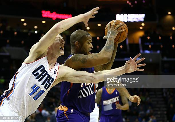 J Tucker of the Phoenix Suns keeps the ball away from Cody Zeller of the Charlotte Bobcats during their game at Time Warner Cable Arena on November...