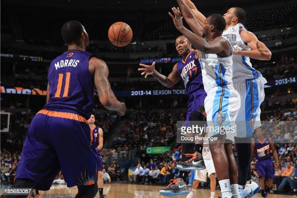 J Tucker of the Phoenix Suns passes the ball to teammate Markieff Morris of the Phoenix Suns against the defense of Jordan Hamilton of the Denver...