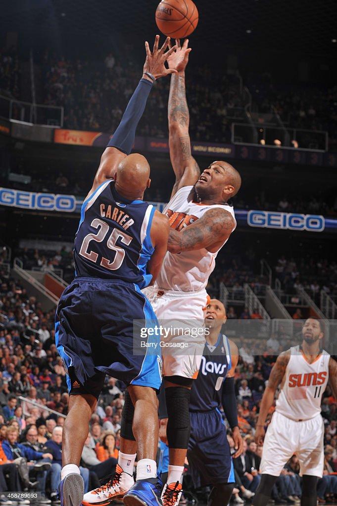 P.J. Tucker #17 of the Phoenix Suns shoots against Vince Carter #25 of the Dallas Mavericks on December 21, 2013 at U.S. Airways Center in Phoenix, Arizona.