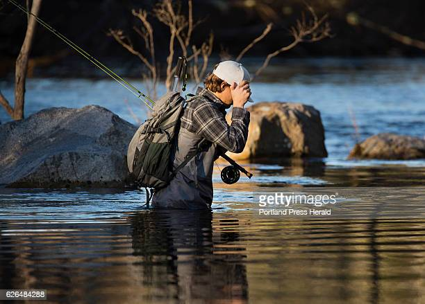 Tucker Van Dusen of Portland shields his eyes from the sun while wading in the Presumpscot River in North Windham, Maine on November 17, 2016....