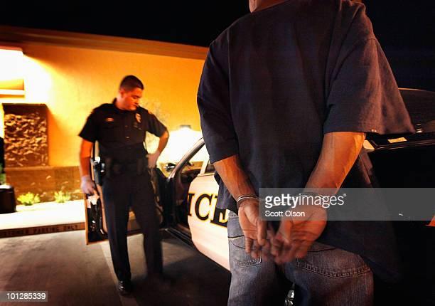 Tucson Police Officer Angel Ramirez arrests a man for trespassing May 29, 2010 in Tucson, Arizona. Ramirez works in the city's predominately Hispanic...