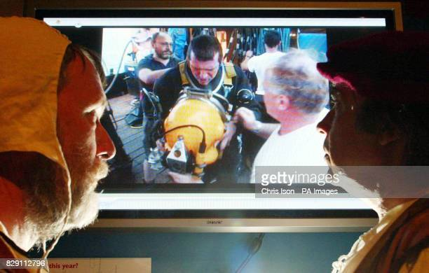 Tudor period costumed interpreters Paul Clair and Colin Pratt at the Mary Rose Museum Portsmouth Dockyard watch footage of divers preparing to dive...