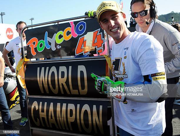 """Tuenti HP 40 rider Pol Espargaro of Spain displays a """"World Champion"""" sign board at the parc ferme after his victory in the Moto2 race of the..."""