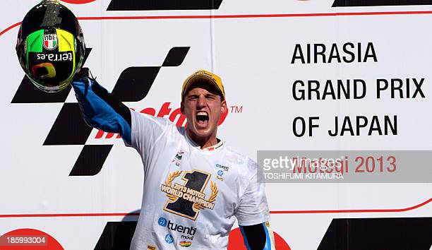 Tuenti HP 40 rider Pol Espargaro of Spain shouts to celebrate taking winning the world title, on the podium after his victory in the Moto2 race of...