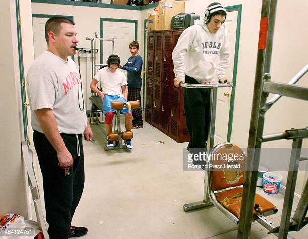 Noble wrestling coach Kip DeVoll drills some of his team on a Universal Gym circuit Doing dips is Jake Badger one of the team's starters