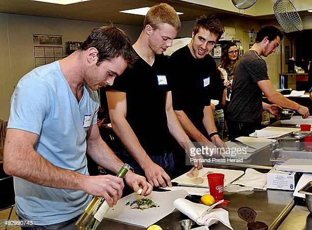 Tuesday November 27 2012 Jordan Szwarz left pours white wine on his fish dish as teammates Mark Visentin and Ethan Werek are in various stages of the...