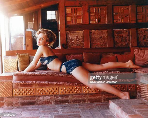 Tuesday Weld US actress wearing a dark blue bikini as she reclines on a sofa circa 1960