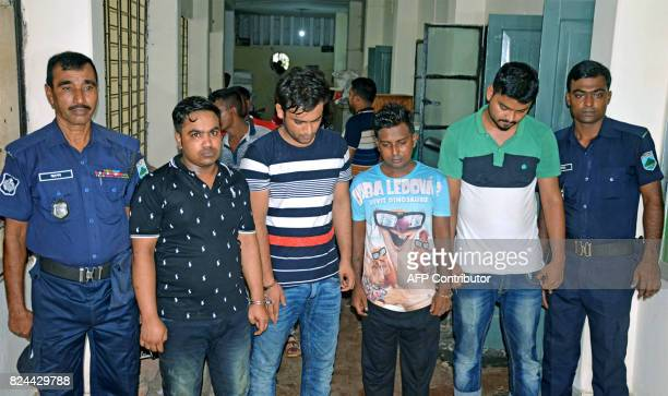 Tufan Sarker a labour leader linked with the ruling Awami League party along with three of his associates is escorted by police following their...