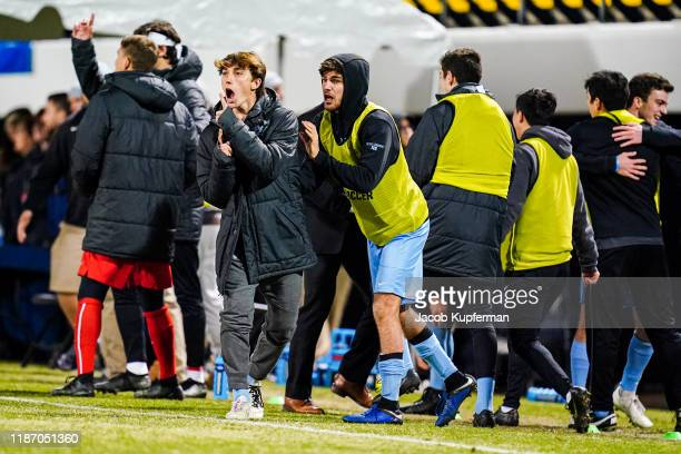 Tufts Jumbos players on the bench cheer on their team after the first goal during the Division III Men's Soccer Championship held at UNCG Soccer...