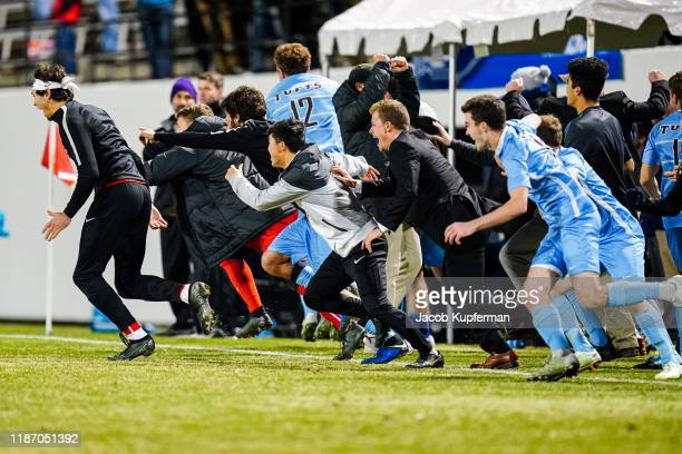 Tufts Jumbos players rush the field at the end of the game during the Division III Men's Soccer Championship held at UNCG Soccer Stadium on December...