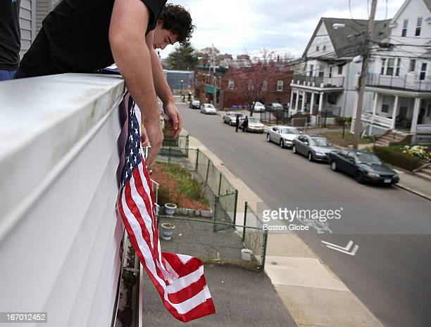 Tufts University students Gary Grandonico left and Tomas Isman right hang an American flag from the porch in honor of their neighbor Sean Collier an...