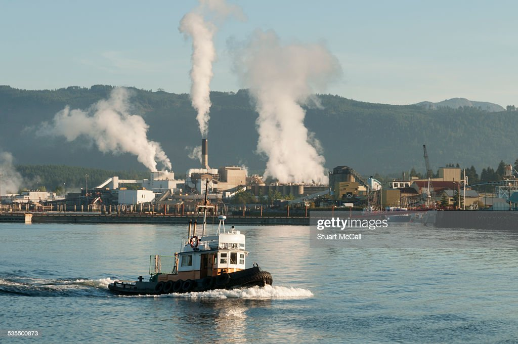 Tug Boat And Pulp Mill On West Coast Of Canada Stock Photo