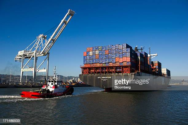 A tug boat moves the APL Singapore container ship to dock at the Port of Oakland in Oakland California US on Thursday June 20 2013 The US Commerce...