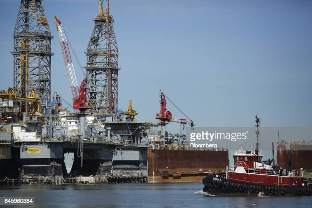 Tug boat passes in front of a dry dock and Ensco Plc oil drilling platforms at the Port of Galveston in Galveston, Texas, U.S., on Thursday, Feb. 16,...