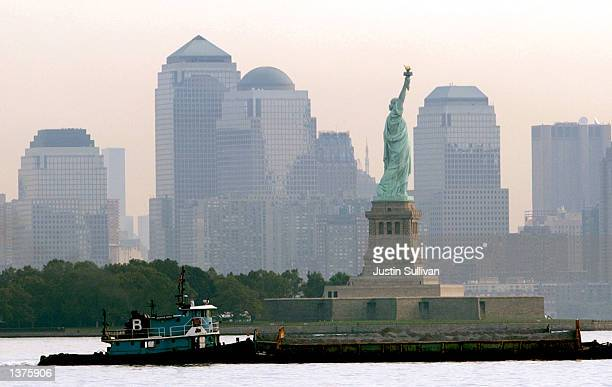 Tug boat passes in front of the Statue of Liberty with the lower Manhattan skyline in the background September 10, 2002 as seen from Bayonne, New...