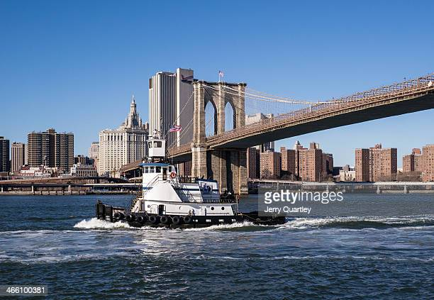 CONTENT] Tug boat passing under the Brooklyn Bridge in winter