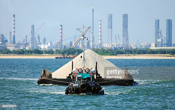 A tug boat pulls a load of sand bound for land reclaimation in southwestern Singapore Thursday Aug 23 2007 Shipyards and petrochemical plants operate...