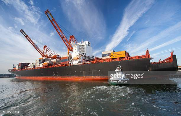tug boat pushing cargo ship into dock as viewed from water - jake warga stock pictures, royalty-free photos & images