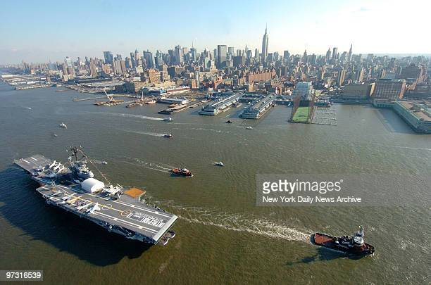 Tug boats guide the USS Intrepid down the Hudson River to Bayonne NJ where it will undergo a twoyear $60 million renovation The historic000ton...