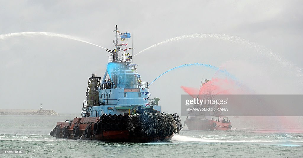 Tug boats put on a water display during the launch the Chinese-built Colombo International Container Terminal (CICT) at the port in Colombo on August 5, 2013. Sri Lanka launched its biggest port with Chinese funding to turn Colombo into a strategic shipping hub along the world's most lucrative trading route. AFP PHOTO/ Ishara S. KODIKARA