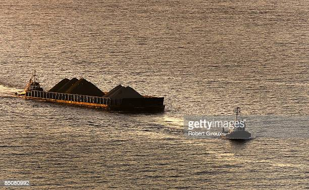 Tug boats tow a barge in Burrard Inlet at sunset February 19 2009 in Vancouver British Columbia Canada Vancouver is the host city for the 2010 Winter...