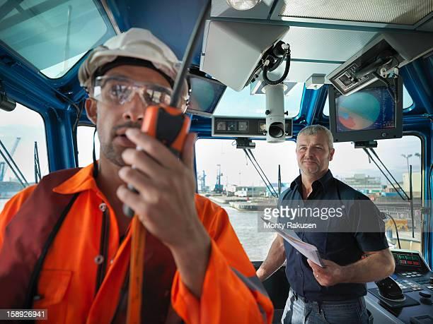 Tug captain and tug worker with radio on bridge of tug