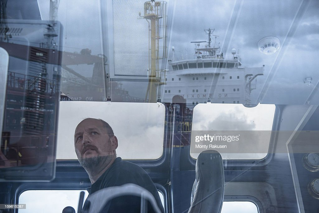 Tug captain looking into distance, with reflections of ship on glass : Stock Photo