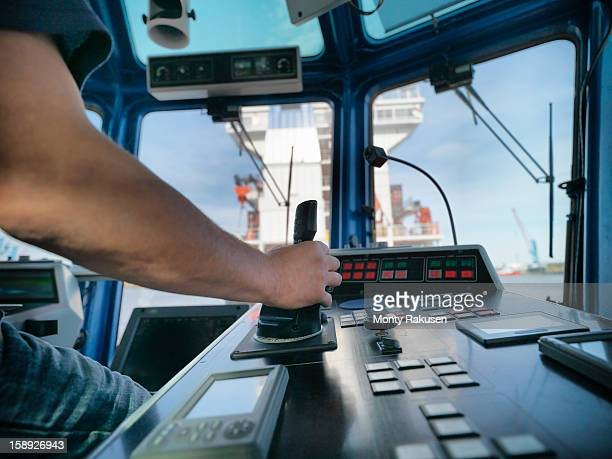 tug captain steering tug with hand on controls - team captain stock pictures, royalty-free photos & images