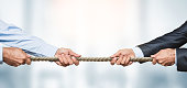 Tug of war, two businessman pulling a rope in opposite directions