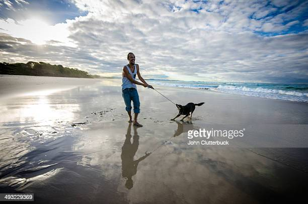 tug of war with dog on beach - dogs tug of war stock pictures, royalty-free photos & images