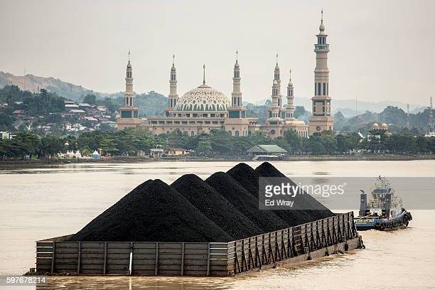 Tug pulls a coal barge past the Islamic centre on August 26, 2016 in Samarinda, Kalimantan, Indonesia. Indonesia's East Kalimantan was reported to be...
